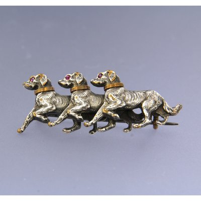 Below legal gold content with silver three dog brooch set with ruby
