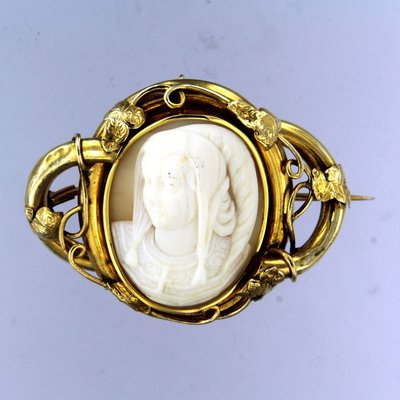 Golden cameo brooch with an image of a child