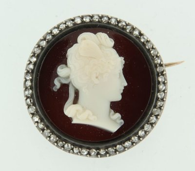 Gold with silver brooch set with onyx and white agate, and 0.80 ct diamond